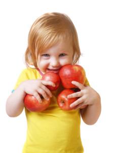 junges Mädchen mit vielen roten Äpfeln in den Händen